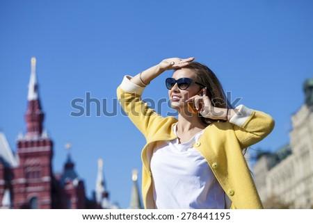 Happy beautiful girl calling by phone in yellow coat - stock photo