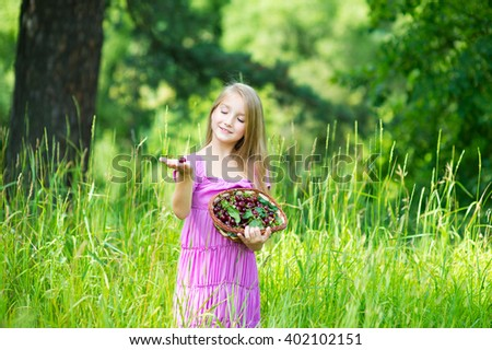 Happy beautiful girl in pink dress with long hair holding basket of fresh cherry harvest in hand and smile in green garden with flowers