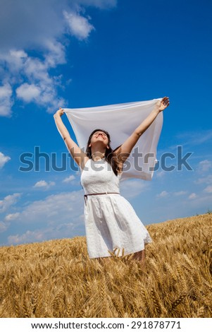 Happy beautiful girl raising her hands with fabric through a field of wheat and enjoying life - stock photo