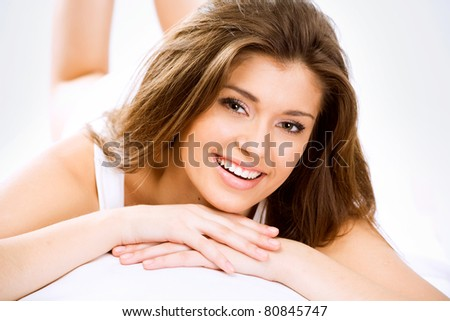 Happy beautiful girl resting on the bed - stock photo