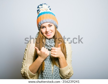 happy beautiful girl showing everything is OK, knit cap, winter concept, photo studio, portrait of a woman isolated on gray background - stock photo