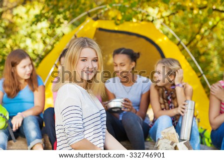 Happy beautiful girl sits near tent with friends