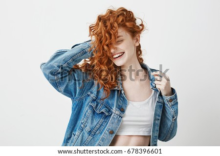 Happy beautiful girl smiling with closed eyes touching her red curly hair over white background.