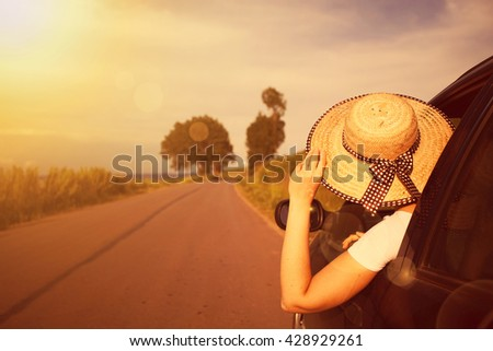 Happy beautiful girl traveling in a car across Europe. Freedom, travel and vacation road trip concept lifestyle image.