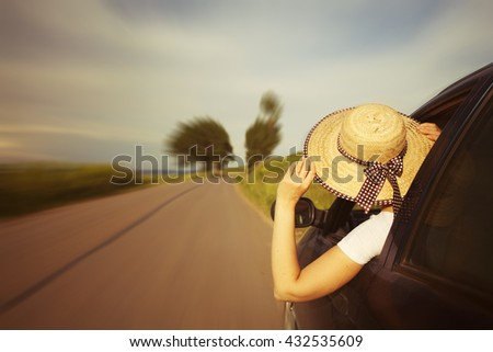 Happy beautiful girl traveling in a car across Europe. Freedom, travel and vacation road trip concept lifestyle image. - stock photo
