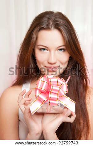 Happy beautiful girl unpacks gift - stock photo