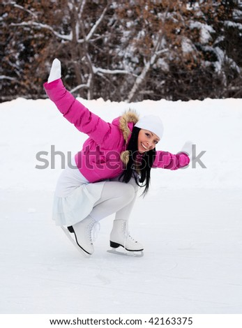 happy beautiful girl wearing warm winter clothes ice skating