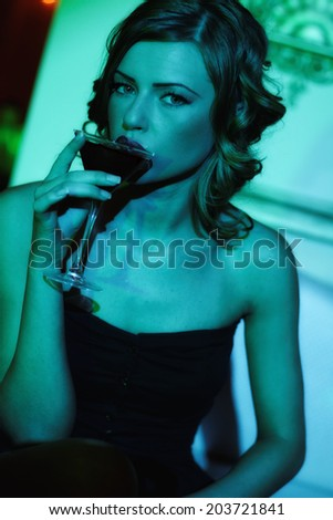 Happy beautiful girl with a drink in nightclub  - stock photo