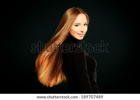 Happy beautiful girl with magnificent long hair in motion posing over black background. - stock photo