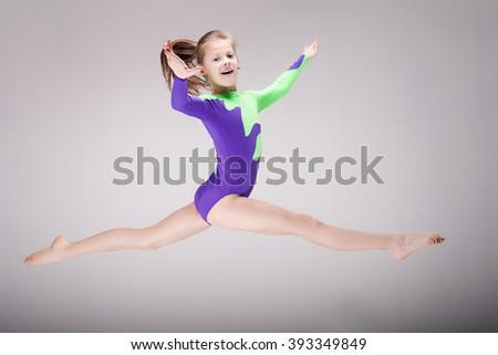 Happy beautiful gymnastic girl. Studio background.  - stock photo
