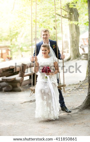 Happy beautiful just married couple posing on swing at park - stock photo