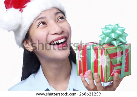 Happy beautiful lady with christmas gift looking upward. Isolated in white background. - stock photo
