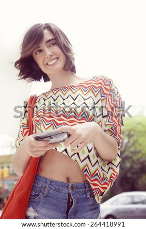Happy beautiful latin woman in the city with mobile phone, sending text message - stock photo