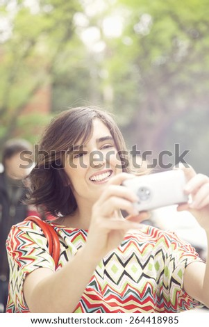 Happy beautiful latin woman in the city with mobile phone, taking self portait - stock photo