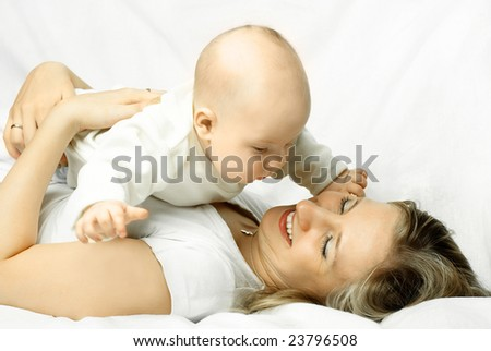 happy beautiful laughing mother lies on the sofa with her baby - stock photo