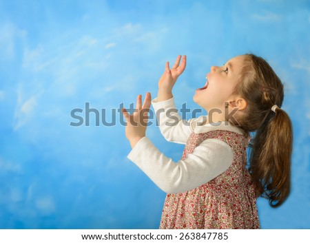 Happy beautiful little girl screaming with her hands up on blue background, studio shot. Little girl playing pretending to be a lion - stock photo