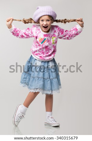 Happy beautiful little girl standing posing in the studio, wearing colorful sweater and blue denim skirt, violet knitted hat and white sneakers. - stock photo
