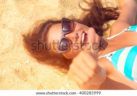 Happy Beautiful model girl in Sunglasses having fun on the Beach. Summer Vacation. Laughing female enjoying Nature, lying on sand. Attractive young Woman at the Beach. Thumb up. Sun Tanning - stock photo