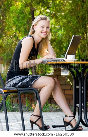 Happy beautiful model sitting in cafe with laptop - stock photo