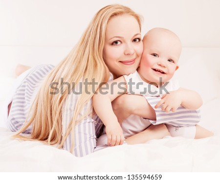 happy beautiful mother and baby in bed at home - stock photo