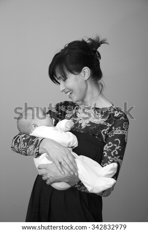 Happy beautiful mother with a baby in hands, monochrome