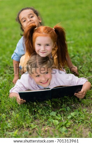 happy beautiful multiethnic schoolgirls reading book while lying on green grass