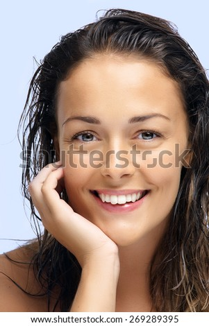 Happy beautiful natural Caucasian woman with dark wet hair.
