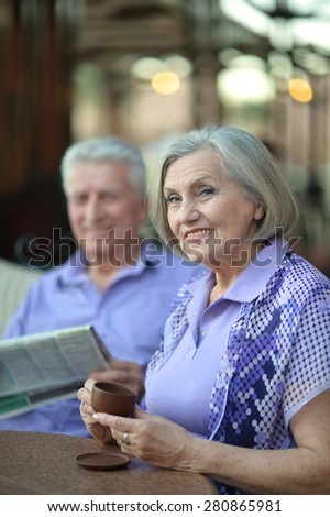 Happy beautiful older couple drink coffee together
