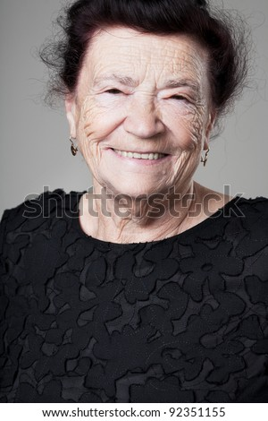 Happy beautiful older lady posing on gray background. - stock photo