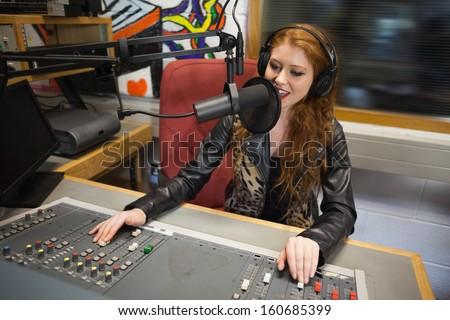 Happy beautiful radio host moderating sitting in studio at college - stock photo