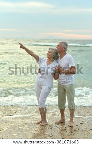 Happy beautiful senior couple hugging on beach - stock photo