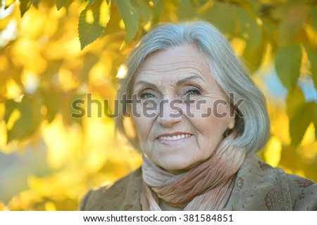 Happy beautiful senior woman in the autumn park - stock photo