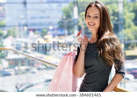 Happy beautiful sexy woman with shopping bags indoor.