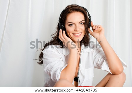 Happy beautiful, slim, attractive brunette woman in Bello shirt and short shorts sitting on the bed and listening to music on headphones - stock photo
