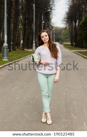 Happy beautiful smiling woman in fashion outfit on white and green background - stock photo