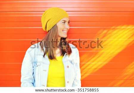 Happy beautiful smiling woman wearing a colorful clothes in city, view profile, looking away - stock photo