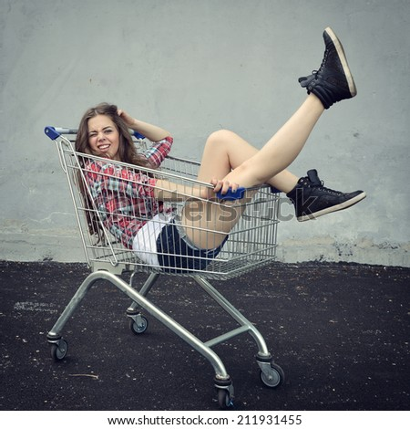 Happy beautiful teen girl driving shopping cart outdoor, image toned and noise added. - stock photo