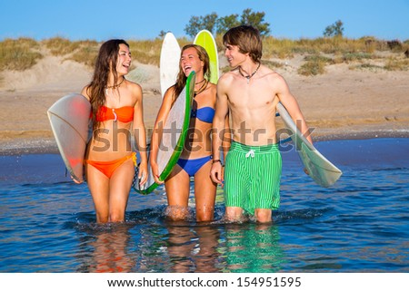 Happy beautiful teen surfers talking on beach shore smiling
