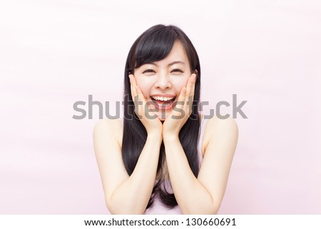 happy beautiful woman against pale pink background - stock photo