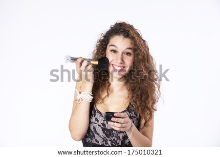 Happy beautiful woman applying some powder brush in her face - stock photo