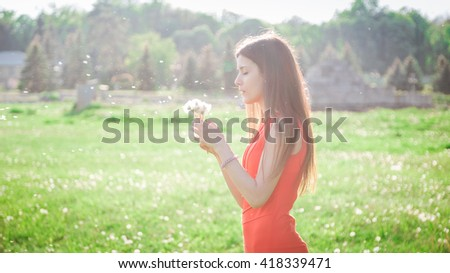 Happy beautiful woman blowing dandelion over sky background, having fun and playing outdoor, enjoying nature, summer vacation and holidays, young pretty female holding flower - stock photo