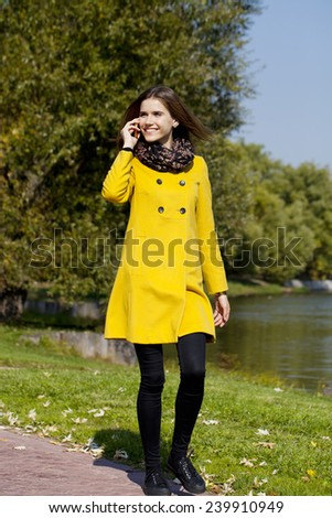 Happy beautiful woman calling by phone in autumn street - stock photo