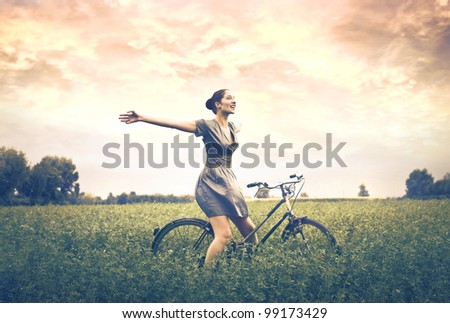 Happy beautiful woman cycling on a green meadow - stock photo