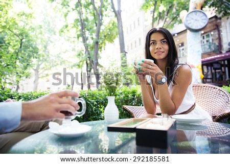 Happy beautiful woman drinking coffee in outdoors cafe - stock photo