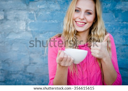 Happy beautiful woman drinking from a cup and showing thumb up - stock photo
