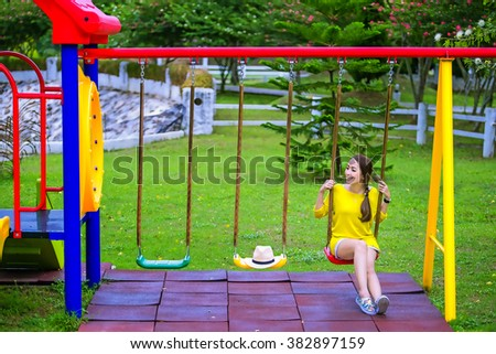 happy beautiful woman having fun on a swing in a Playground