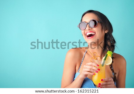 Happy beautiful woman holding a tropical cocktail with sunglasses on bright background  - stock photo