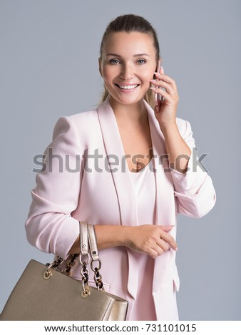 Happy beautiful woman holds handbag and mobile over white background