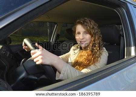 Happy beautiful woman in a car - stock photo