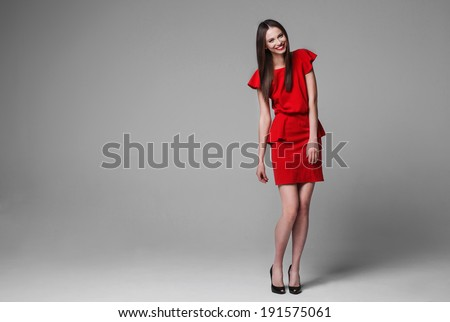 Happy beautiful woman in red dress smiling - stock photo